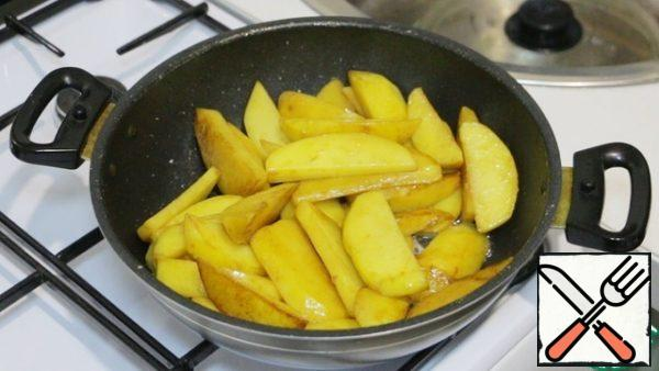 Then in the same oil fry large slices of potatoes under a closed lid. Stir occasionally and do not forget to add salt. With a fork, check the readiness of potatoes. Ready potatoes spread on a separate plate.