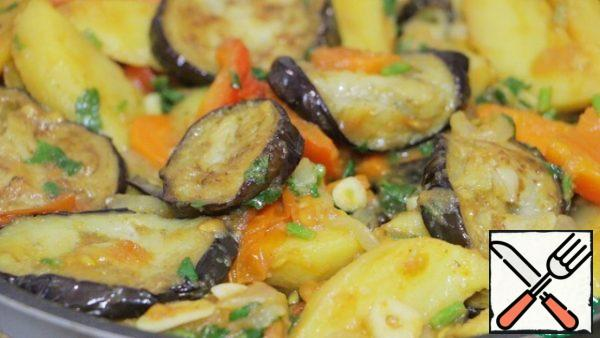 Gradually add all remaining ingredients to the stewed vegetables. First of all, put the potatoes and gently mix everything, followed by a couple of minutes are garlic and cilantro, then all the seasonings and last of all add eggplant. Stir slowly and carefully so that the dish does not turn into porridge. Put out all together a couple of minutes and turn off the fire. Leave the dish a little more languish under the lid.