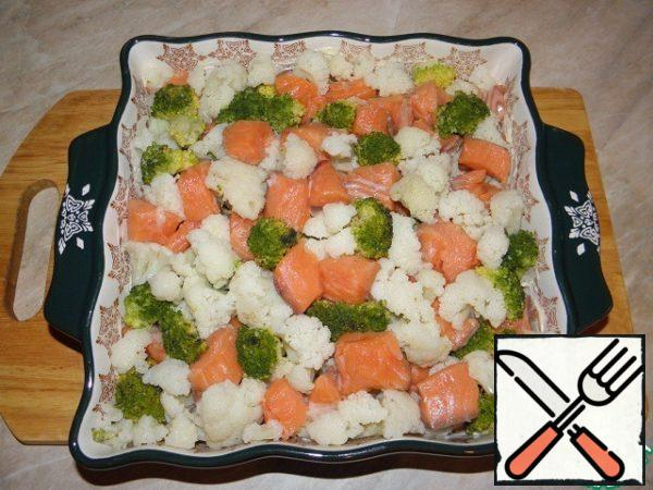 Baking dish with high sides smeared with butter, boiled color and broccoli cabbage and fish spread in the form.