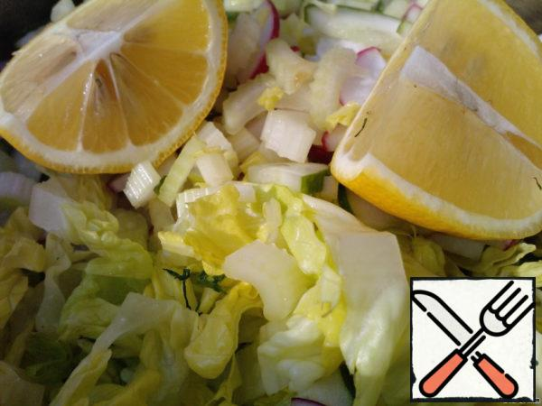 Squeeze the juice of a small lemon into a mixture of vegetables and herbs.