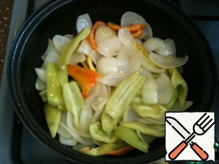 In a frying pan heat the Rast. oil, put the onion (onions) and fry it for 1-2 minutes until Golden brown over medium heat. Then add the pepper, stir and cook for 1-2 minutes also.