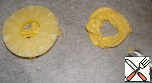 Baking sheet covered with baking paper. The dough is spread in a pastry syringe or bag. And in a circular motion squeezing on paper the basis for cakes. Put a piece of pineapple on top, lightly press the dough under the pineapple should protrude from under the pineapple.