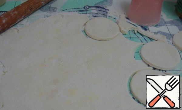 The cooled dough is rolled into a layer 1 cm thick, cut out of it with round shapes of different diameters of the cake of two sizes.