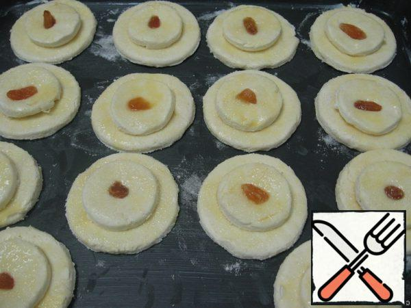 Little cakes to put on large, top - twist, to put pressure on it with your finger. Put the cheesecakes on a baking sheet, greased with margarine. Refrigerate for 20 minutes.