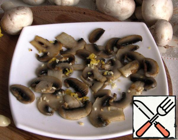 Sprinkle fried mushrooms with zest and garlic, pour lemon juice.