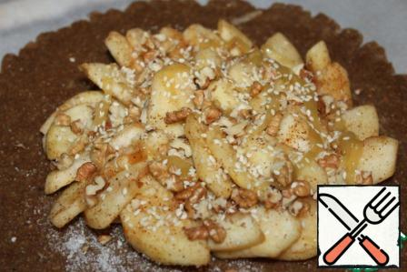 Spread the apples-also in the center, leaving the edges of the dough free, pour honey, sprinkle with nuts and sesame seeds.