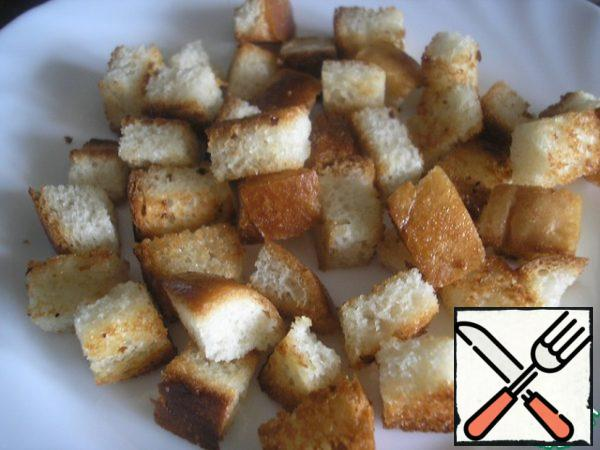 It is very convenient to serve this salad in portions. We will need 4 salad bowls.Prepare the croutons. Cut the slices of the loaf into cubes of about 1x1 cm. Heat 1 tablespoon of oil in a pan. Over high heat, quickly fry the bread cubes, stirring constantly. Cool them down. It is important that the crackers turned out with a crispy crust, but soft inside.