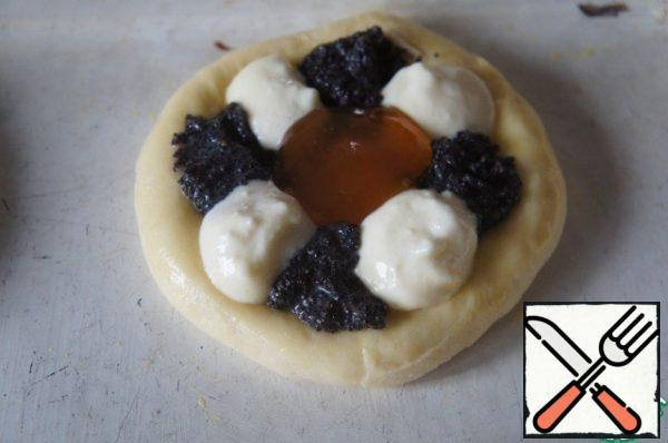 In the middle of a teaspoon staggered put cottage cheese and poppy seed filling, and put jam in the center.