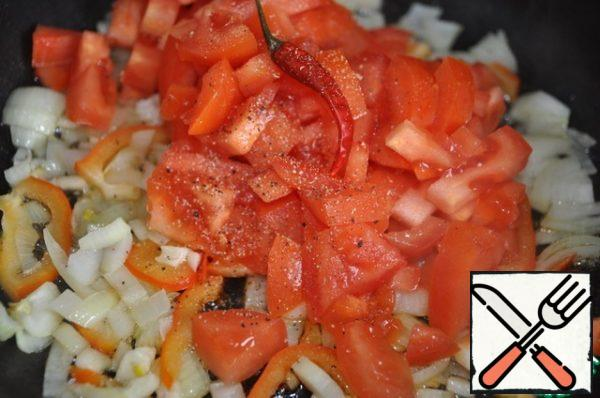 In the pan put a piece of butter, chopped onions, garlic and bell pepper, fry for 2 minutes. Add finely chopped tomatoes, red ground hot pepper, black pepper and salt. Mix everything and simmer for 10 minutes.