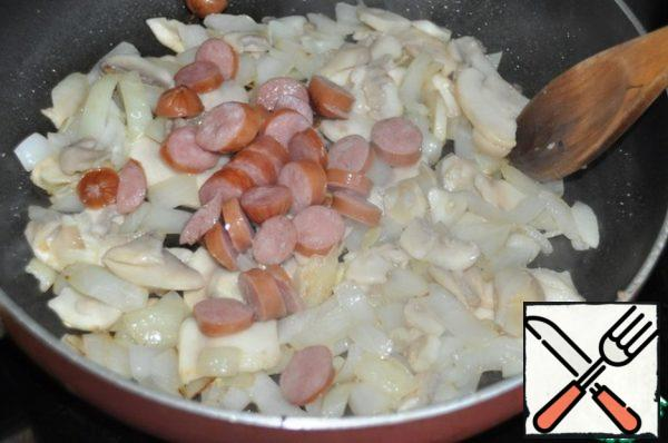 Put the cut rings hunting sausages. You can add ham or bacon, all fry and simmer for 8 minutes.