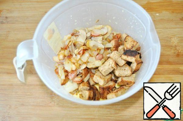 Add to the omelet mixture dried bread, fried mushrooms.