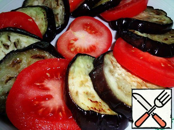 Spread the vegetables on a plate, alternating cooled eggplants and tomatoes. Do not add salt.