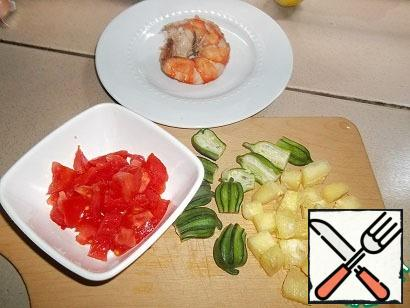"""While seafood is marinated, okra (or as we call this vegetable """"Gombo"""") cut along, removing the stalks. If the okra is large, cut into rings. Pineapple and tomatoes cut into small cubes. Get the seafood with a slotted spoon from the pan. In the boiling broth add the prepared okra, pineapple and tomatoes. Cook over medium heat for 10 minutes. Lid not to close, run away."""