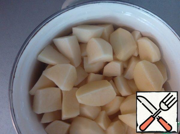 Potatoes clean, wash, cut into 4 parts.