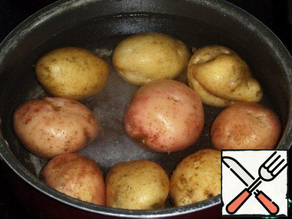 Potatoes are washed. Spread in a saucepan. Add water and salt (1 tsp). Cook until tender. Then drain the water. Potatoes are cooled and cleaned.