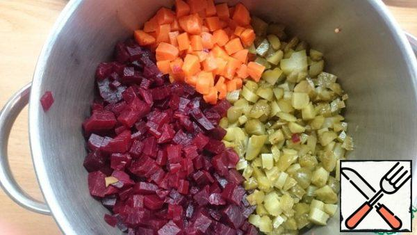 Cook carrots and beets, clean and cut into cubes. Dice the pickled cucumber.