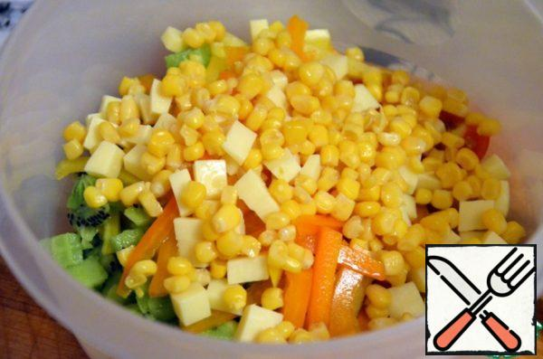 In a salad bowl spread kiwi, pepper, cheese, tomatoes, corn (pre-drained liquid), top pour dressing, sprinkle with sesame seeds.