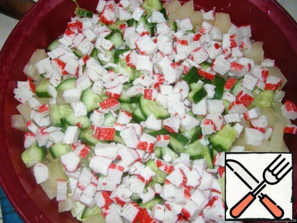 Cut the crab sticks and add to the salad.
