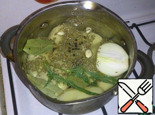 Put the potatoes to boil. Fill the potatoes with cold water. Throw in the water bay leaf, pepper, garlic cloves 2, half onions, Basil and dill. Put on the fire and cook until tender. Salt for ten minutes until ready.