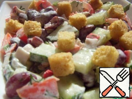 Mix mayonnaise with garlic. To mix the salad, season with salt and sprinkle with croutons.