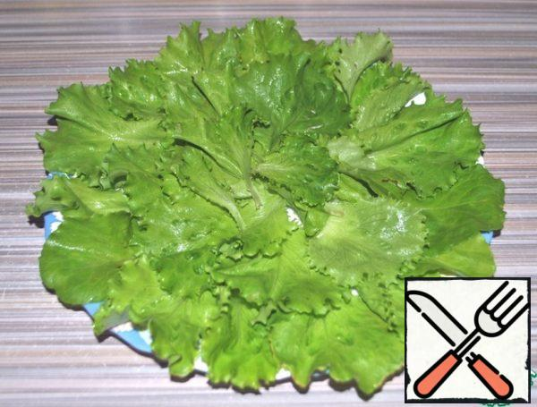 Are starting to collect salad. On the dish lay out lettuce leaves.