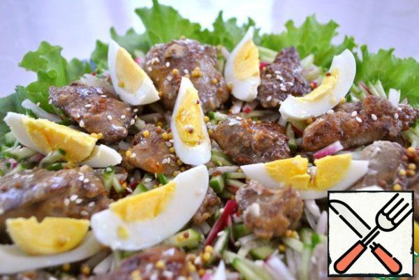 Spread on top the liver and egg. Pour the dressing. If desired, you can sprinkle sesame salad.