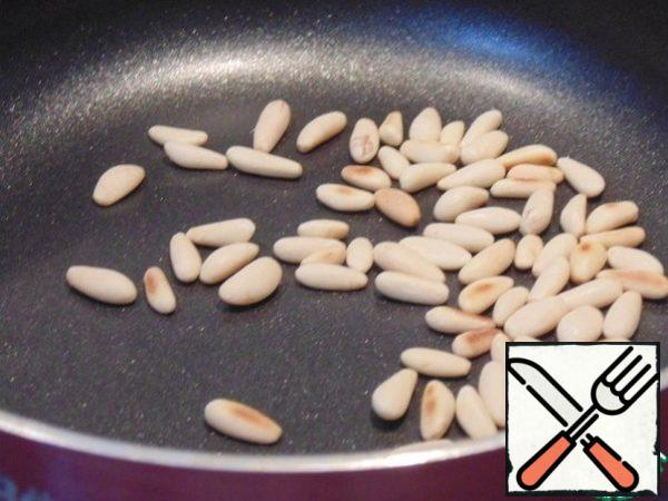 Pine nuts fry in a dry pan. Lettuce wash, dry. Prepare the dressing: mix 1 tablespoon of olive oil with 1 tablespoon of lemon juice, salt and pepper.