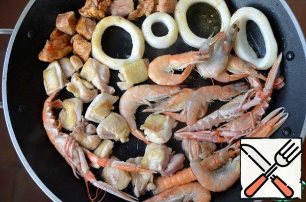 In a frying pan, heat the olive oil and fry the pieces of meat, shrimp and cuttlefish for 2 minutes on each side and put on a plate.