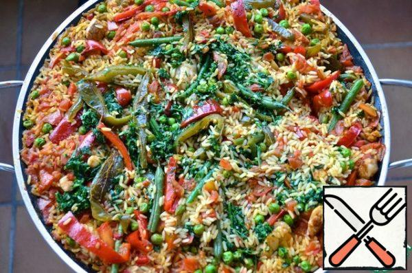 Sprinkle with paella mixture of parsley and garlic. After 10 minutes, reduce the heat and put on paella mussels and shellfish, slightly drowning them in rice. After 4 minutes, put ready-made prawns and cuttlefish on paella. Cook for an additional 4 minutes. In total, after adding rice, paella is cooked for 18 minutes. Turn off the heat, cover the pan and let paella rest for two minutes.