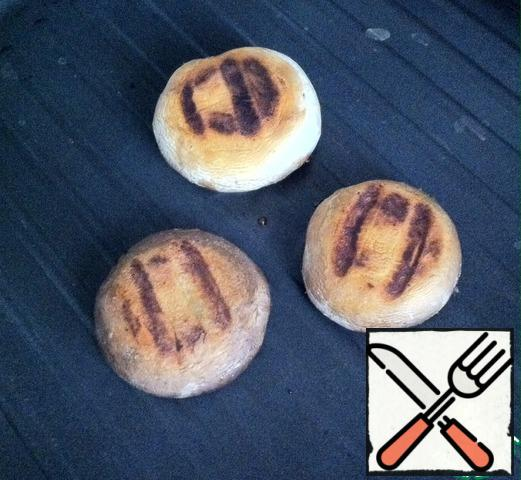 Hats mushrooms grease 1 tbsp. l. vegetable oil and fry in a hot pan-grill until strips.