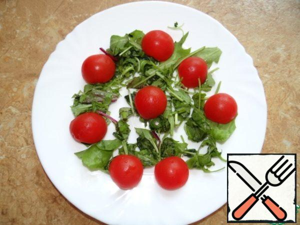 The greens, chop roughly, place in a bowl, add the tomatoes, cut in half;