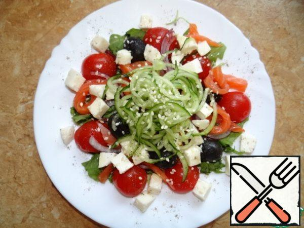 Add trout, cut into thin strips, mozzarella, diced; Decorate the salad with cucumber, sliced thin spiral;