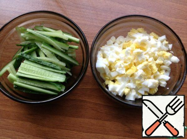 Cucumbers cut into strips, in a separate bowl, chop eggs.