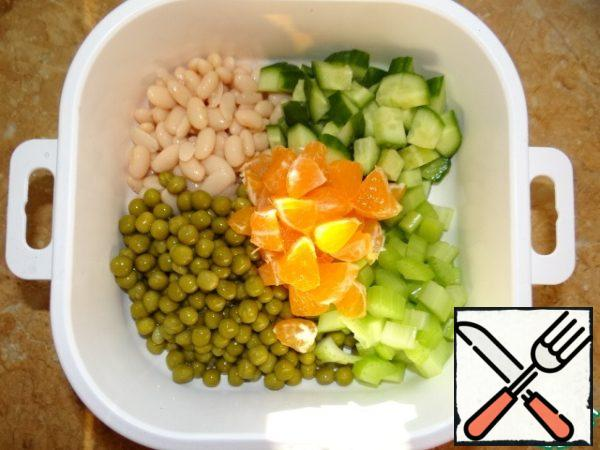 Beans and peas separately throw on a sieve or colander, drain the excess liquid; To add finely cut cucumber, celery and Tangerine;