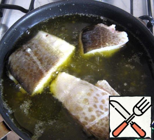 Take out the garlic, let the oil cool slightly, spread the cod. And on the smallest fire we prepare it, moving the pan from side to side.