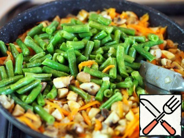 Heat a frying pan with vegetable oil, crush the garlic clove and fry it for 1-2 minutes, then throw it away. In a frying pan, with an interval of 2-3 minutes, put onions, carrots, mushrooms, beans on roasting. If beans are frozen, defrost it first.