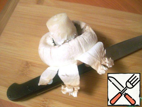 Wash the mushrooms, separate the legs (they are not needed), remove the thin white skin from the hats with a knife.