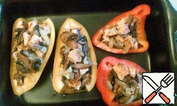 Wash pepper, remove the core and seeds, cut it into 2 halves. Fill the pepper halves with mixed chicken fillet and mushrooms. Put in the oven for 15-20 minutes.