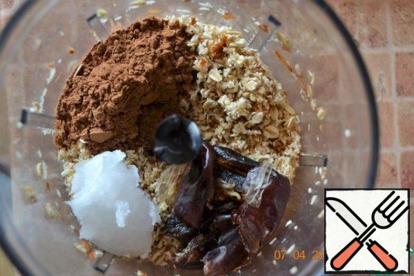 Oat flakes and almonds grind in a blender. By the way, I pre-soaked nuts in water at room temperature for at least 2 hours. This helps to better assimilation and digestion of nuts. Dates wash. Add to the flakes and almonds cocoa powder, coconut oil and dates and grind again.