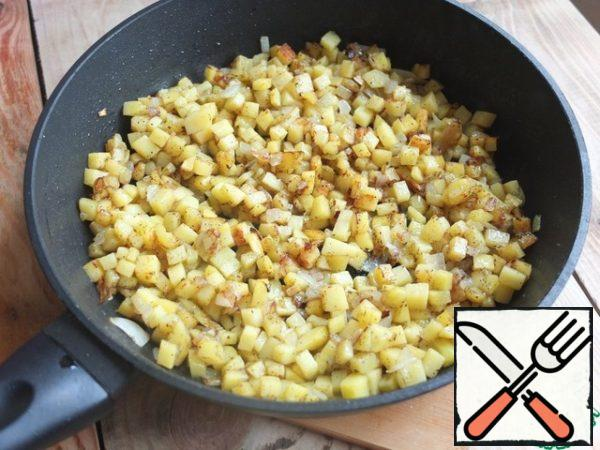 "While the dough is ""resting"", prepare the filling. Finely chop the onion and potatoes. Fry in a small amount of vegetable oil until Golden brown. Salt, pepper (here you can omit it and season the filling after adding minced meat)."