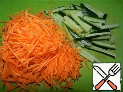 Carrots grate on the grater. Cucumber cut into long bars.