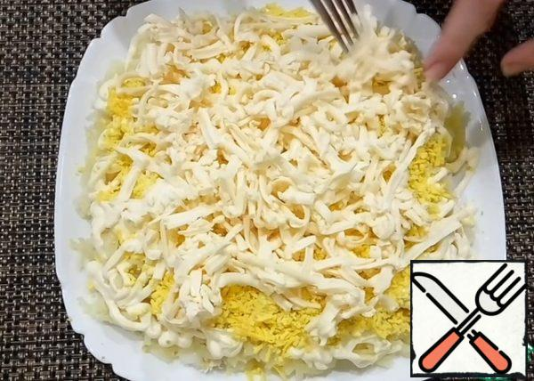 On top of the yolk, grate the processed cheese on a coarse grater. I pre-send cheese in the freezer for 20-30 minutes, it is then easier to RUB.