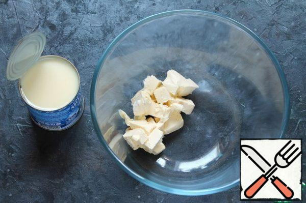 Butter at room temperature, beat with condensed milk.