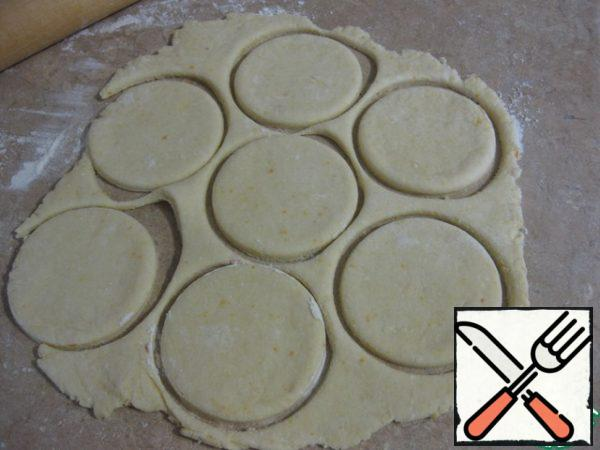 The table sprinkle flour quite slightly, roll out the dough in a circle is not very thin, about 0.3-0.4 cm, cut out circles with a diameter of 8-9 cm.