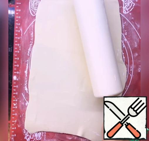 Roll out the dough into a thin layer, sprinkled with a place for rolling starch.
