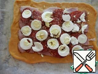 One part of the dough is rolled into a thin rectangular layer. Transfer it to a baking sheet covered with baking paper. Spread on the dough the filling layers - ham, chorizo, onion rings on top of the eggs.