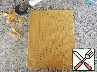 Roll out the second part of the dough into the same rectangle. Put on the filling, pinch the edges. The remaining piece of dough is thinly rolled out, cut into strips. Strips to put mesh on the top of the cake, the edges of the strips attached to the edges of the pie.