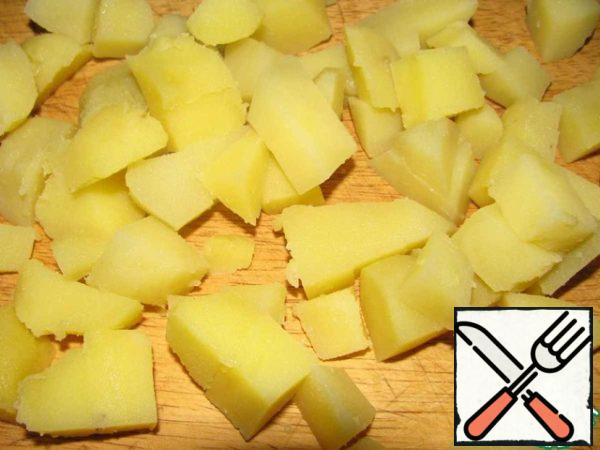 Wash potatoes and cook in the peel for 25 minutes. Drain, cool, peel and cut into cubes.