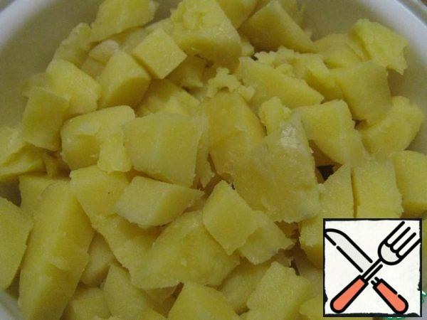 Boil potatoes in salted water until tender. Drain the water. Cool the potatoes and cut them into cubes.