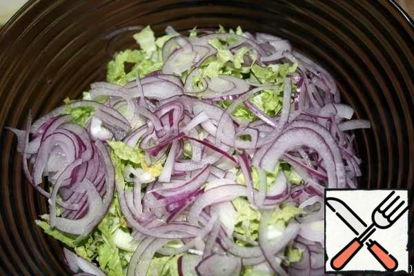 Peel the red onion and cut into thin half-rings. Add to cabbage.